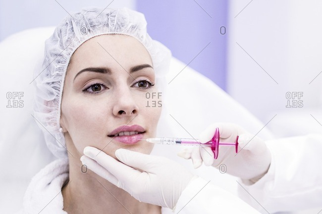 Dermatologist injecting botox into a woman's lips, close-up.