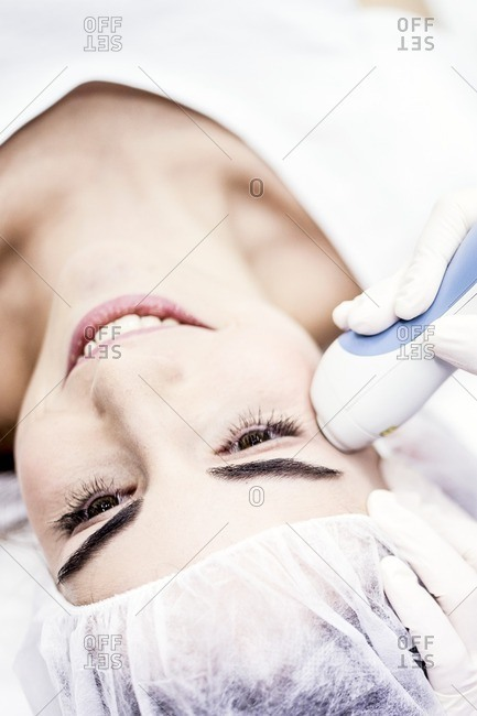 Young woman having laser peeling treatment, close-up. This treatment smooths and rejuvenates the skin.