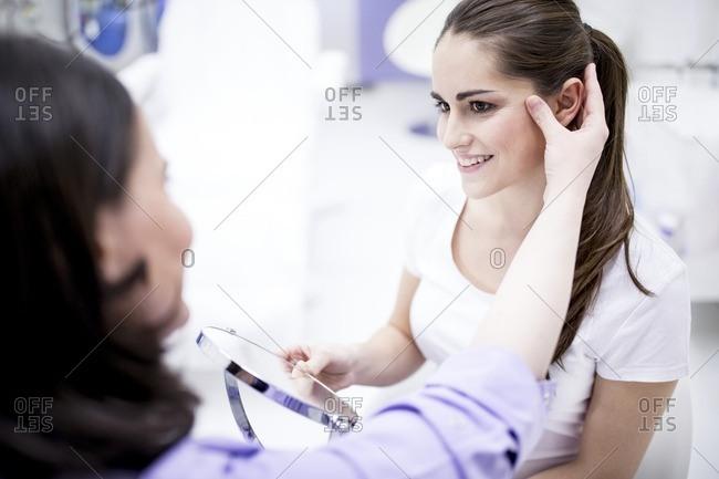 Dermatologist examining patient's facial skin, close-up.