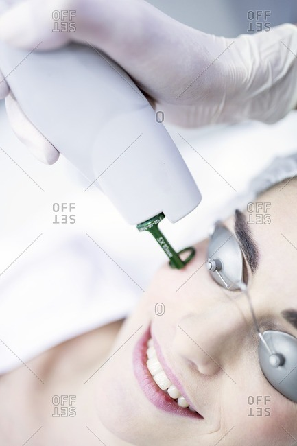 Dermatologist using laser machine on woman's face, close-up.