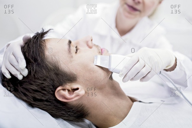 Dermatologist applying facial microdermabrasion treatment on man in clinic, close-up. The cosmetic procedure uses micro crystals to remove dead skin cells. This exfoliating treatment can stimulate the production of collagen and help improve fine lines and acne scarring.