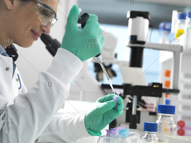 Biotech Research- Scientist pipetting sample into a vial ready for analysis during a experiment in the laboratory
