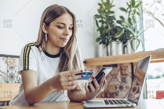 Young woman with credit card and laptop