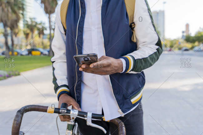 Close-up of casual businessman with bicycle using cell phone in the city- Barcelona- Spain