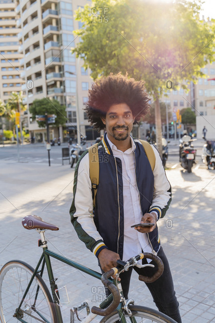 Portrait of smiling casual businessman with bicycle and cell phone in the city- Barcelona- Spain