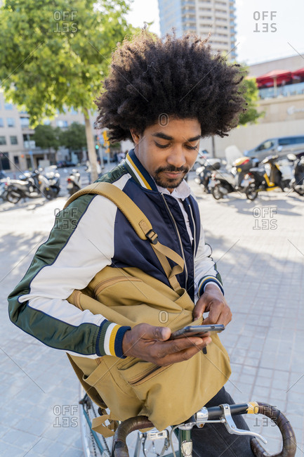 Casual businessman with bicycle using cell phone in the city- Barcelona- Spain