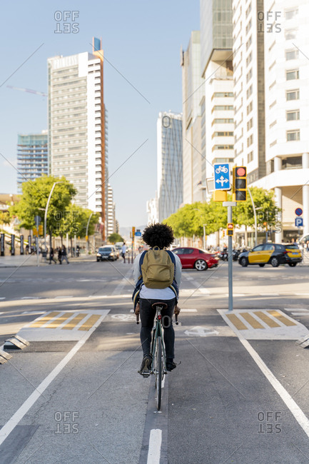 Rear view of casual businessman on bicycle in the city- Barcelona- Spain