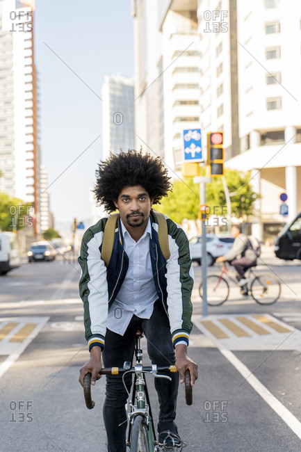Casual businessman on bicycle in the city- Barcelona- Spain