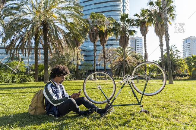 Casual businessman with cell phone and bicycle in urban park- Barcelona- Spain