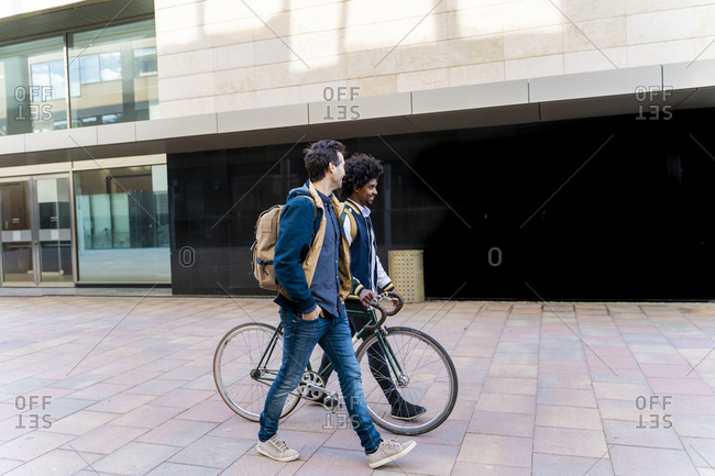 Two casual businessmen with bicycle walking in the city- Barcelona- Spain