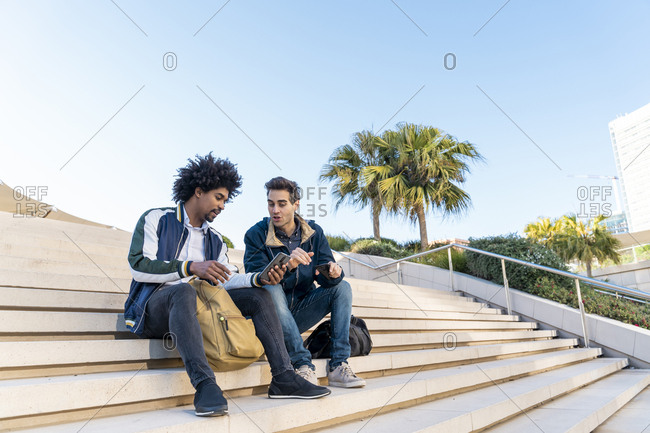 Two casual businessmen sitting on stairs sharing cell phone