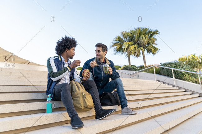 Two casual businessmen sitting on stairs having lunch break