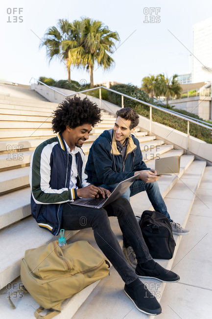 Two casual businessmen sitting on stairs working on laptop
