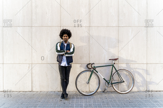 Portrait of casual businessman with bicycle standing at a wall