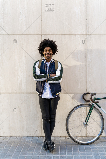 Portrait of smiling casual businessman with bicycle standing at a wall