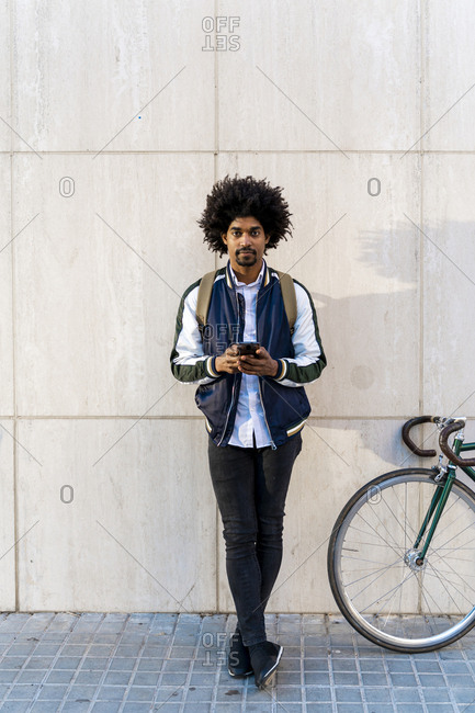 Portrait of casual businessman with bicycle and cell phone standing at a wall