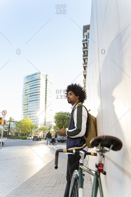 Casual businessman with bicycle and cell phone in the city- Barcelona- Spain