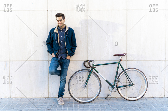 Portrait of casual man with bicycle standing at a wall