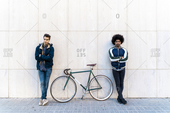Portrait of two casual men with bicycle standing at a wall