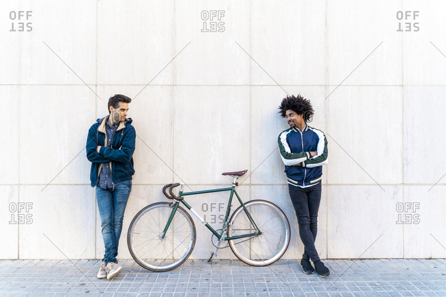 Two casual men with bicycle standing at a wall