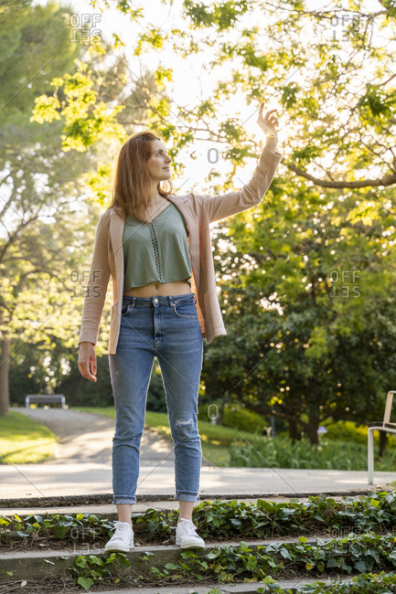 Young redheaded woman touching leave in a park