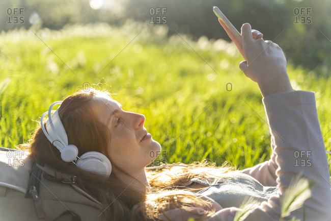 Young redheaded woman with headphones and smartphone in a park