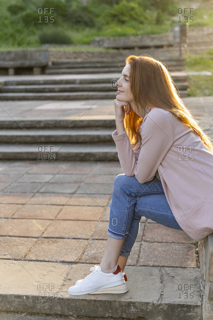 Young redheaded woman sitting in a park