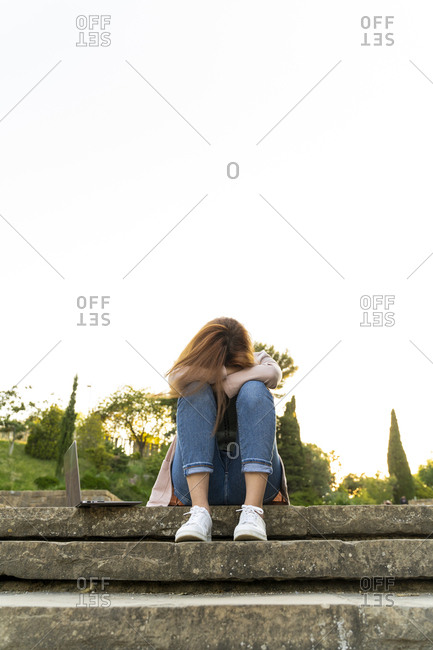 Young redheaded sleeping woman sitting on steps next to a laptop in a park