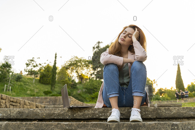 Young redheaded tired woman sitting on steps next to a laptop in a park