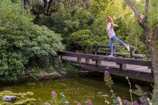 Young redheaded woman balancing on bridge in a park