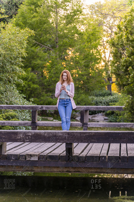 Young redheaded woman using smartphone on a bridge in a park