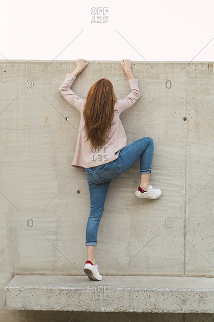 Young redheaded woman climbing on concrete wall