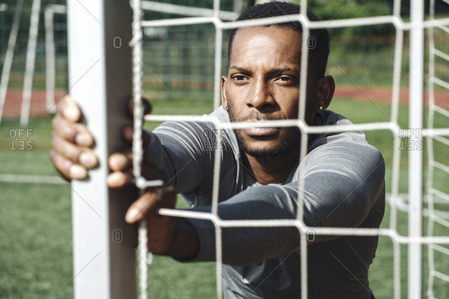 Portrait of sportsman stretching exercise behind net