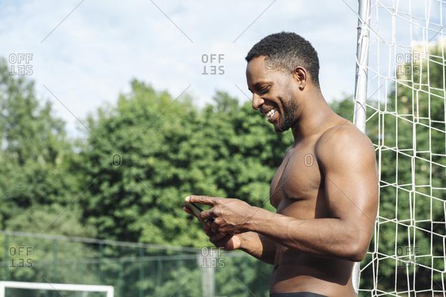 Sportsman using smartphone at soccer field