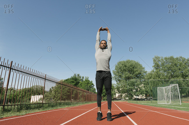 Sportsman stretching his arms on racetrack