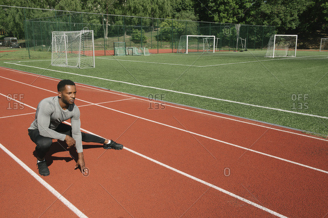 Sportsman stretching his leg on racetrack