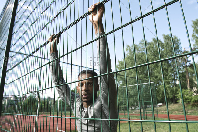 Portrait of sportsman behind fence