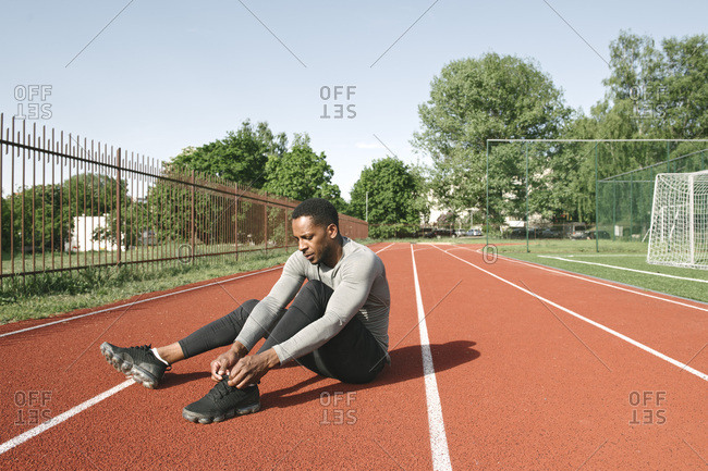 Sportsman sitting on racetrack and tying shoes before workout