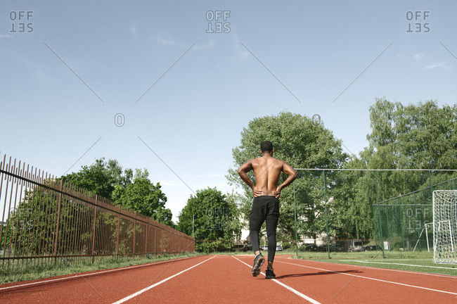Athletic man walking on rubber racetrack- rear view