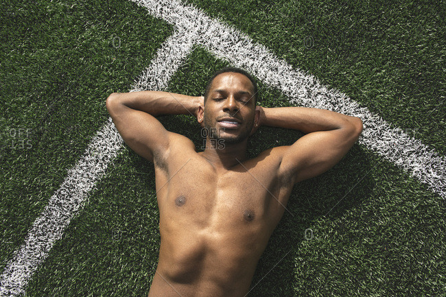 Athlete relaxing after workout on a lawn