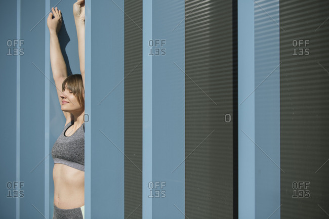 Sportswoman lifting arms in blue wall