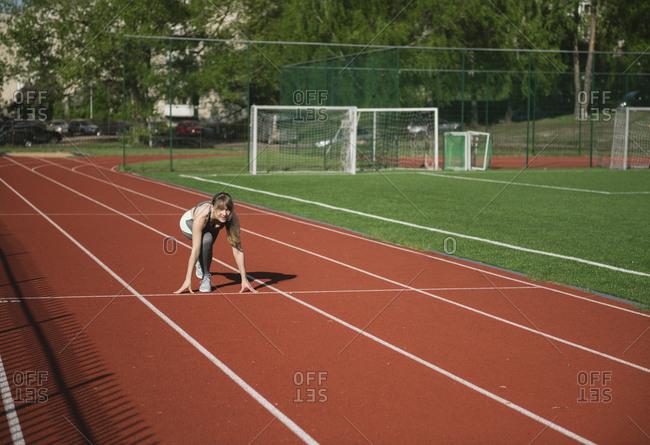 Female runner on tartan track in starting position