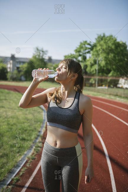 Sportswoman drinking water on racetrack