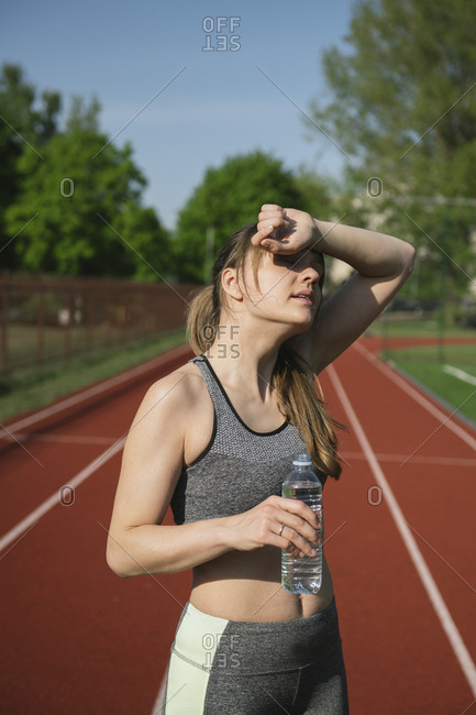 Sportswoman on racetrack drinking water after workout