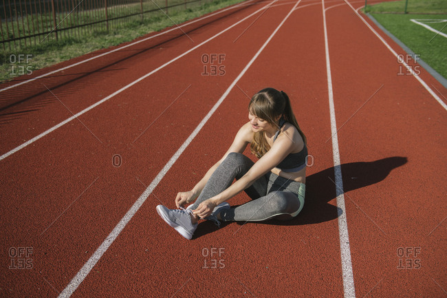 Sportswoman on racetrack tying shoes