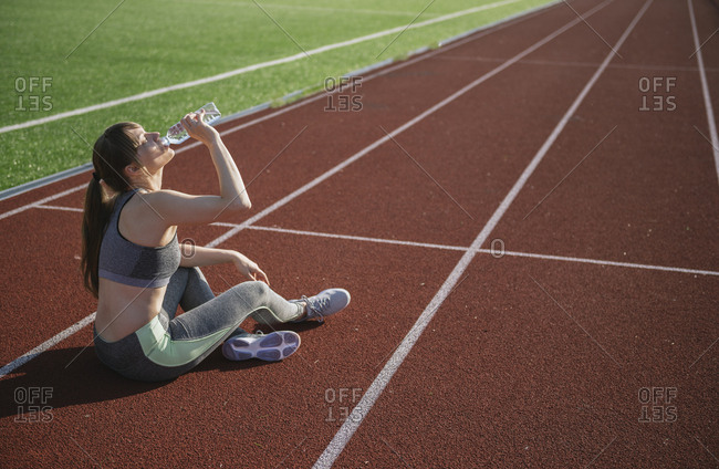 Sportswoman sitting on racetrack and drinking water after workout