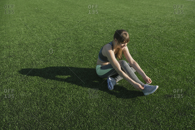 Sportswoman sitting on lawn and tying shoes