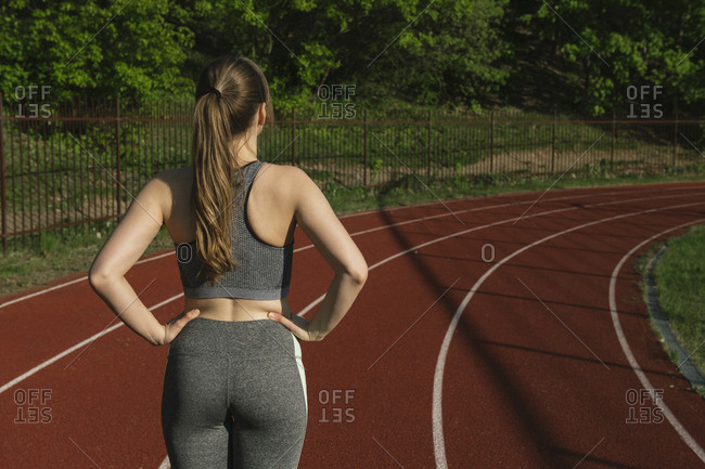 Rear view of sportswoman standing on racetrack