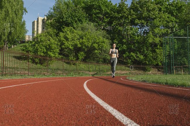 Sportswoman runing on racetrack