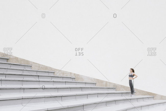 Sportswoman standing and looking up on concrete bleachers